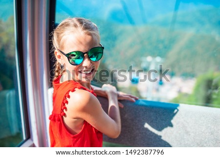 Adorable little girl in the cabin on the cable car in mountains in the background of beautful landscape #1492387796