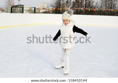 Adorable little girl in the white clothes and hat on the ice rink