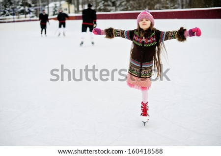 Adorable little girl in winter clothes and bobble hat skating on ice rink #160418588