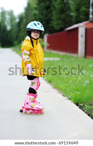 Adorable little girl in yellow raincoat, blue helmet and pink roller-skates