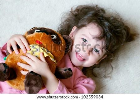 Adorable little girl is hugging big teddy bear