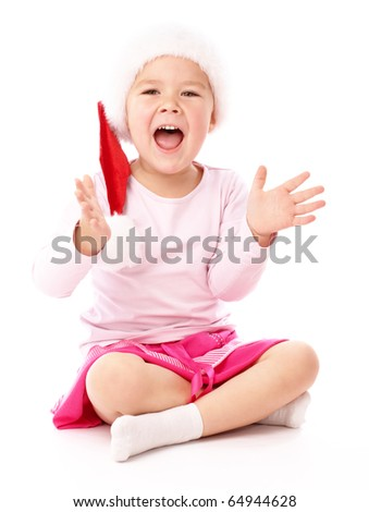 Adorable little girl is sitting on floor and clapping her hands, wearing red Christmas cap, isolated over white