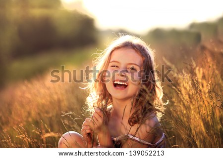 Adorable little girl laughing in a meadow - happy girl