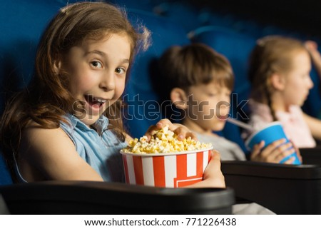 Adorable little girl looking excitedly to the camera enjoying movie premiere at the local cinema holding big popcorn bucket copyspace lifestyle entertainment activity leisure spectator concept