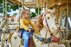 Adorable little girl on the playground. Preschooler having fun on vintage French merry-go-round in Paris. Outdoor activities for small kids