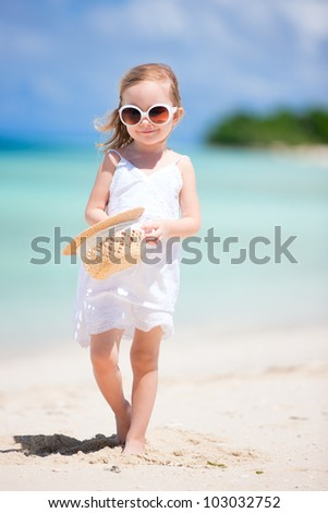 Adorable little girl on tropical beach vacation