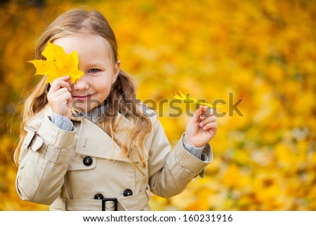 Adorable little girl outdoors at beautiful autumn day