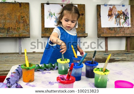 Adorable little girl painting and drawing.Concept photo of art, artwork, creativity and imagination.