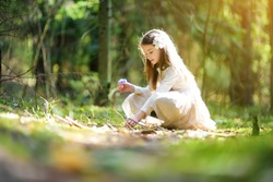 Adorable little girl picking the first flowers of spring in the woods on beautiful sunny spring day. Cute child having fun outdoors.