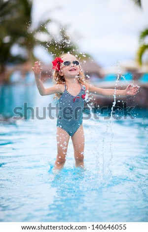 Adorable little girl playing at a swimming pool