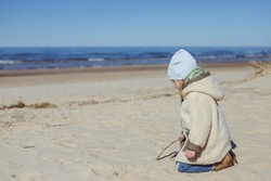 Adorable little girl playing by the ocean on spring day. Family enjoying walk in nature.