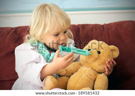 Adorable little girl playing doctor with her teddy bear