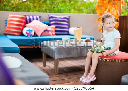 Adorable little girl playing on a tablet device