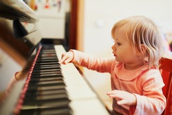Adorable little girl playing piano. Toddler having fun while learning how to play music. Musical education for small kids