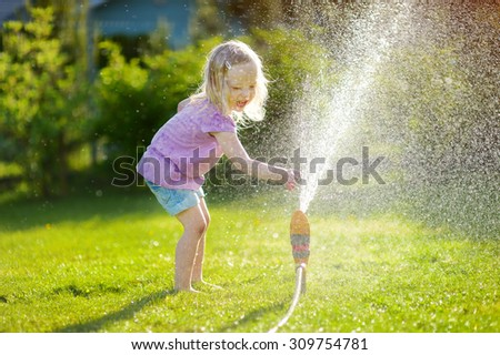 Adorable little girl playing with a sprinkler in a backyard on sunny summer day