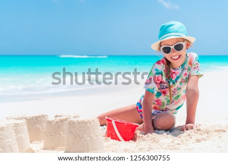 Adorable little girl playing with beach toys during summer vacation #1256300755