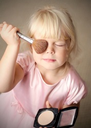 Adorable little girl playing with mommy's make up
