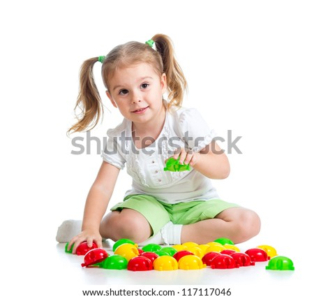 Adorable little girl playing with  mosaic toy