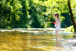 Adorable little girl playing with paper boats by a river on warm and sunny summer day