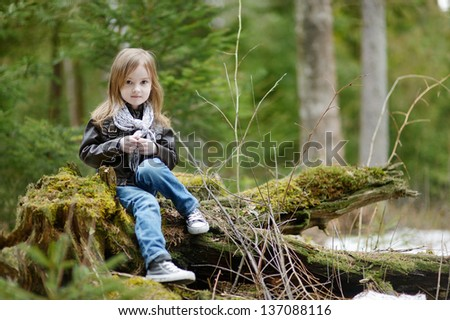 Adorable little girl portrait outdoors at spring or autumn