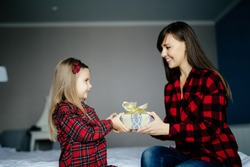Adorable little girl presenting gift to happy mother on Mothers Day