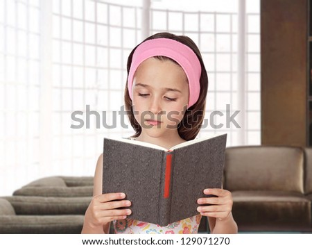 Adorable little girl reading a book in her home