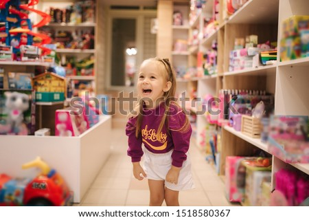 Adorable little girl shopping for toys. Cute female in toy store. Happy young girl selecting toy
