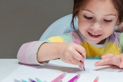 Adorable little girl sitting at the table and drawing with felt-tip pens on a white sheet of paper. gray background.