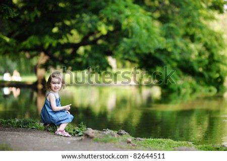 Adorable little girl sitting by the water