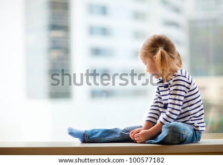 Adorable little girl sitting by the window