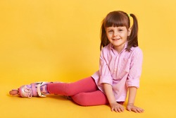 Adorable little girl sitting on floor. Concept of happy childhood. Funny female kid with two ponytails posing isolated over yellow background, wearing rolling skates casual red leggins and rose tunic.