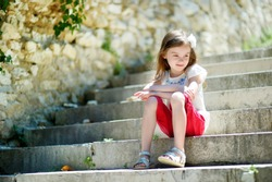 Adorable little girl sitting on stairs on warm and sunny summer day in typical italian town
