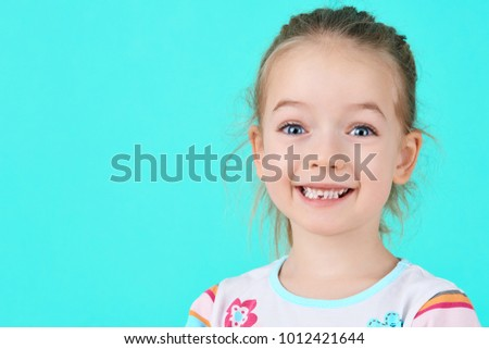 Adorable little girl smiling and showing off her first lost milk tooth. Cute preschooler portrait after dropping her front baby tooth.