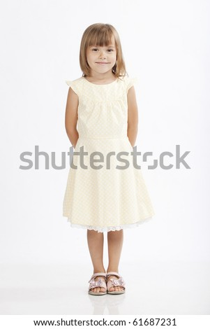 Adorable little girl standing and hiding her hands