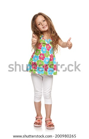 Adorable little girl standing in full length and showing double thumbs up, over white background