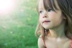 Adorable little girl taken closeup outdoors in summer - lighting effect
