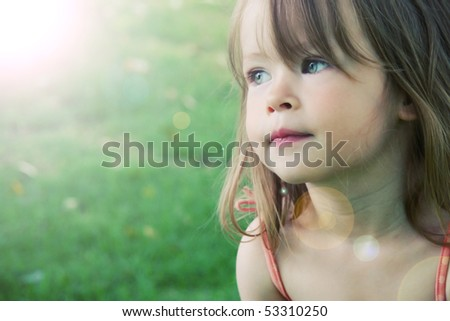 Adorable little girl taken closeup outdoors in summer lighting effect