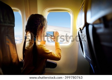 Adorable little girl traveling by an airplane. Child sitting by aircraft window and looking outside. #399780763