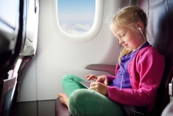 Adorable little girl traveling by an airplane. Child sitting by aircraft window and using a digital tablet during the flight. Traveling abroad with kids.