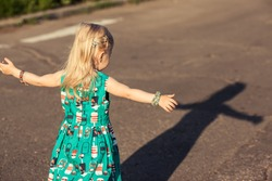 Adorable little girl trying to catch her shadow