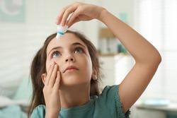 Adorable little girl using eye drops indoors