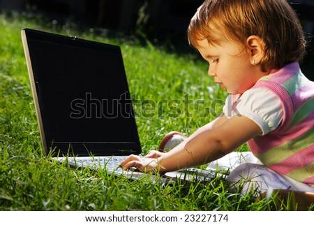 Adorable little girl using laptop on green grass