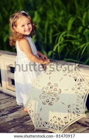 adorable little girl walking in the park with sun umbrella