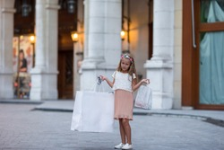 Adorable little girl walking with shopping bags in Paris outdoors