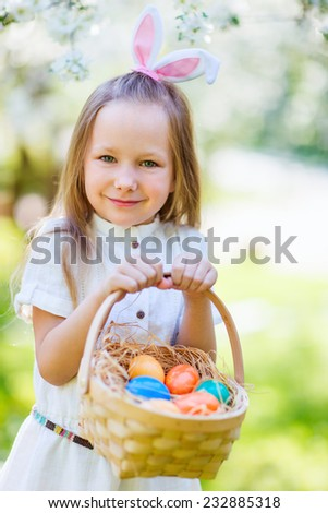 Adorable little girl wearing bunny ears playing with Easter eggs in a blooming garden on spring day #232885318