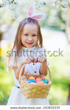 Adorable little girl wearing bunny ears playing with Easter eggs in a blooming garden on spring day #243850159