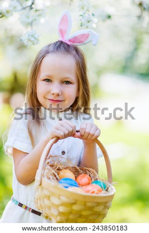 Adorable little girl wearing bunny ears playing with Easter eggs in a blooming garden on spring day #243850183