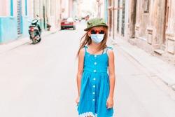 Adorable little girl wearing face mask on street in Old Havana, Cuba