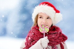 Adorable little girl wearing Santa hat having huge striped Christmas lollipop on beautiful winter day. Child with lolly candy on Xmas day.