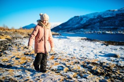 Adorable little girl wearing warm clothes outdoors on beautiful winter day